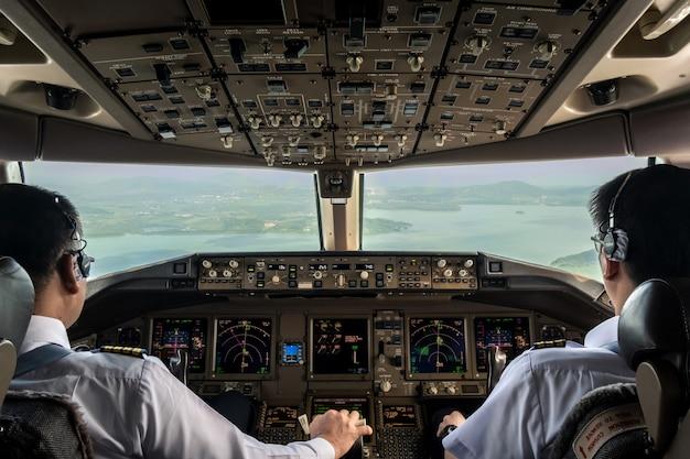 Cabina di pilotaggio interna dell'aereo commerciale mentre vola avvicinandosi alla pista.