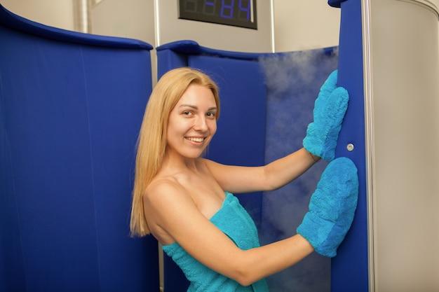 Cabina entrante di sauna di crioterapia della donna dai capelli biondi