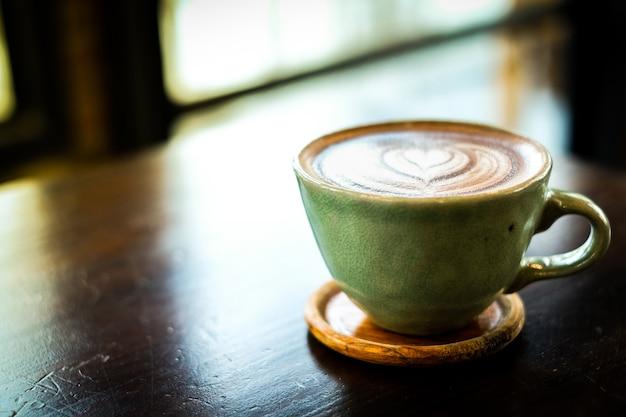 Cacao caldo caldo fatto in casa (caffè) con schiuma di latte bianca fantasia sulla superficie in tazza