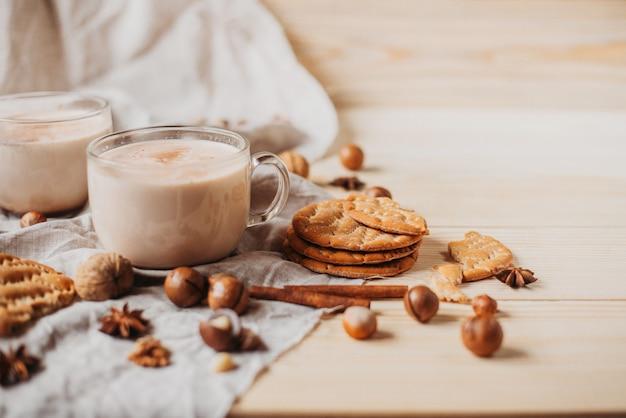 Cacao caldo con biscotti, bastoncini di cannella, anice, noci sul tavolo di legno. vista frontale, copia spazio.