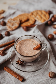 Cacao caldo con biscotti, bastoncini di cannella, anice, noci sul tavolo di legno.