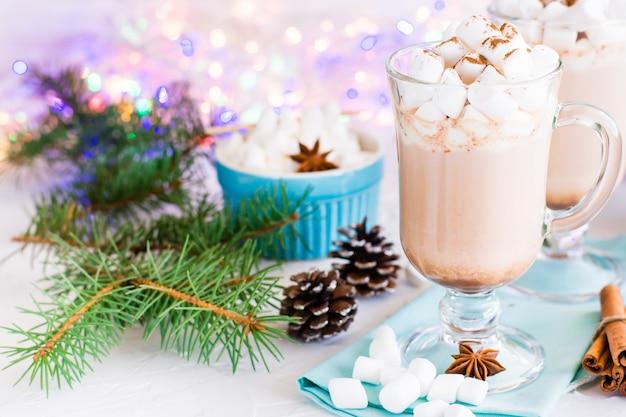 Cacao caldo con marshmallow e cannella macinata in bicchieri con decorazioni natalizie
