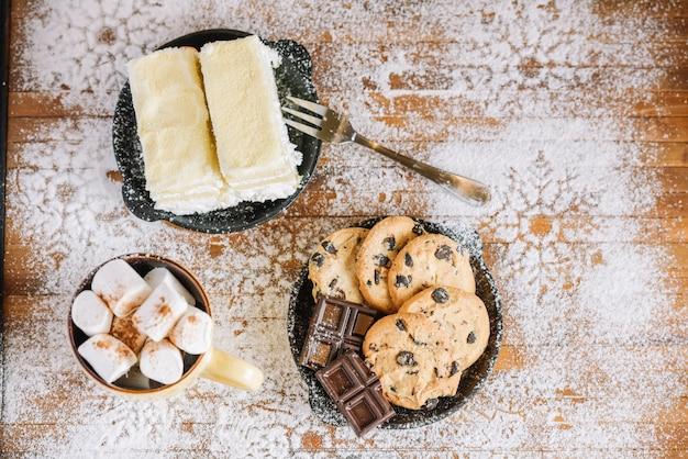 Cacao con dolci su tavolo decorato con zucchero a velo