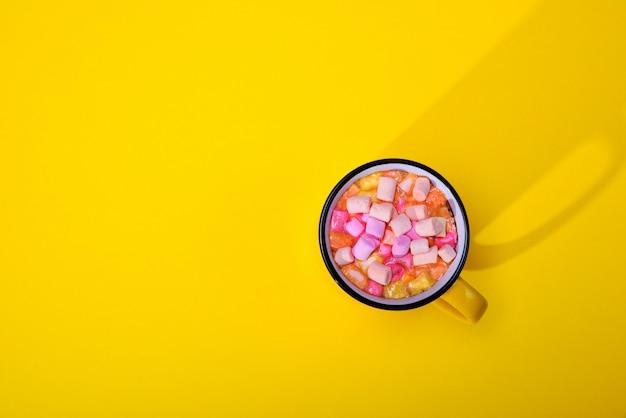 Cacao con fette di marshmallow in una tazza gialla, vista dall'alto, spazio vuoto