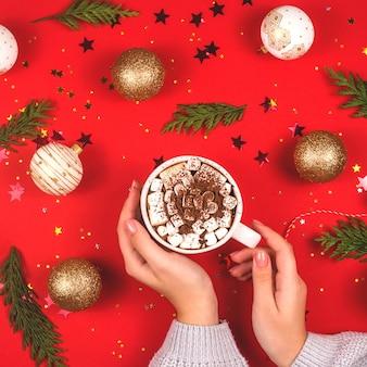 Cacao con marshmallow in mani femminili tra le decorazioni natalizie su rosso.