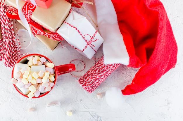 Cacao con marshmallow in tazza rossa, scatole regalo