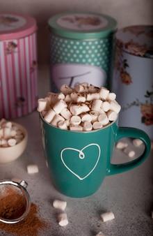 Cacao con marshmallow in un bicchiere verde