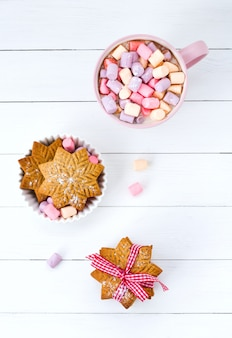 Cacao di natale con marshmallow in una tazza rosa e biscotto allo zenzero su un tavolo di legno
