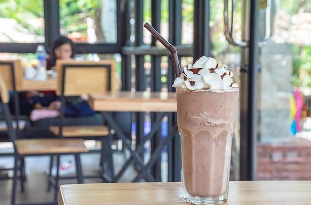 Cacao freddo con panna montata in cima su un tavolo di legno