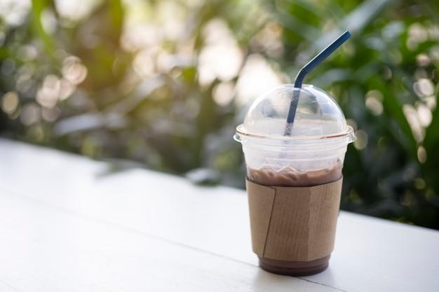 Cacao ghiacciato in tazza di plastica sui precedenti di verde della tavola