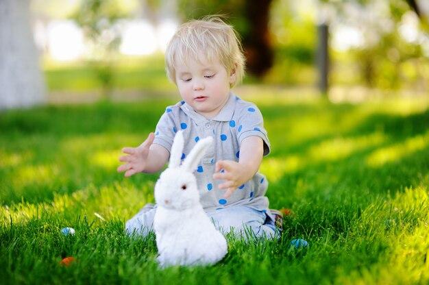 Caccia del ragazzino per l'uovo di pasqua nel giardino di primavera il giorno di pasqua. piccolo bambino sveglio con coniglietto tradizionale che celebra la festa