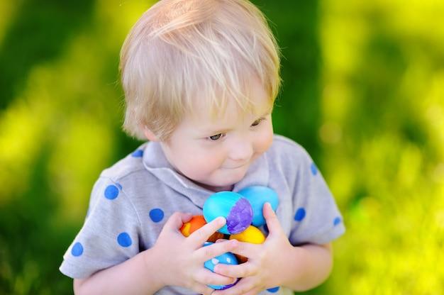Caccia del ragazzino per l'uovo di pasqua nel giardino di primavera il giorno di pasqua.