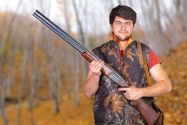 Cacciatore con il suo fucile in una foresta