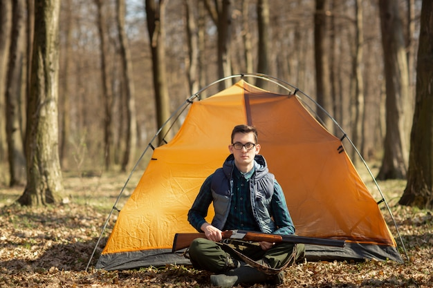 Cacciatore con una pistola nella foresta seduto vicino alla tenda