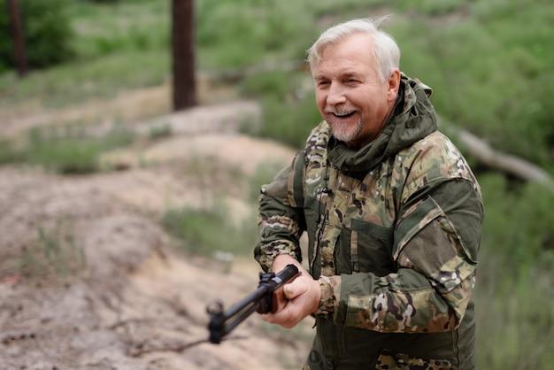 Cacciatore felice cammina con il concetto di stile di vita del fucile da caccia.