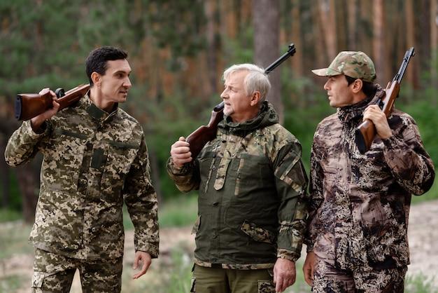Cacciatori spensierati uomini che camminano nella foresta di pini.