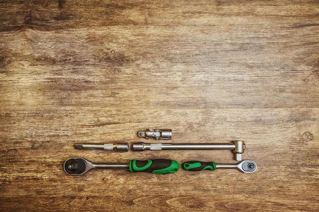 Cacciavite con cricchetto. set di attrezzi diversi su fondo di legno.