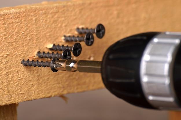 Cacciavite su un tavolo di legno avvitato con viti