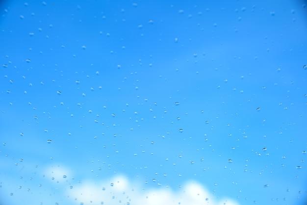 Cada l'acqua in vetro sulla priorità bassa del cielo blu della sfuocatura