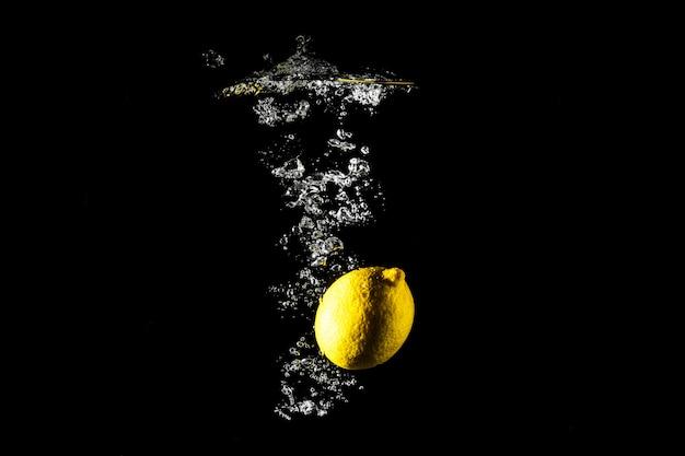 Caduta del limone nel fondo del nero dell'acqua.
