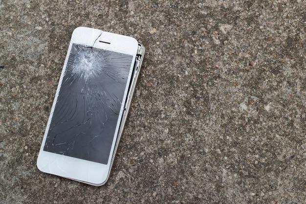 Caduta mobile smartphone sul pavimento di cemento con touch screen bro