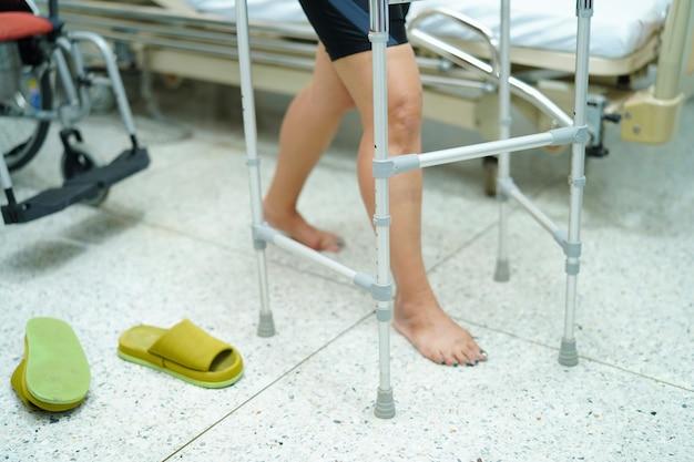 Caduta paziente della donna di signora di mezza età asiatica ed uso del camminatore in salone