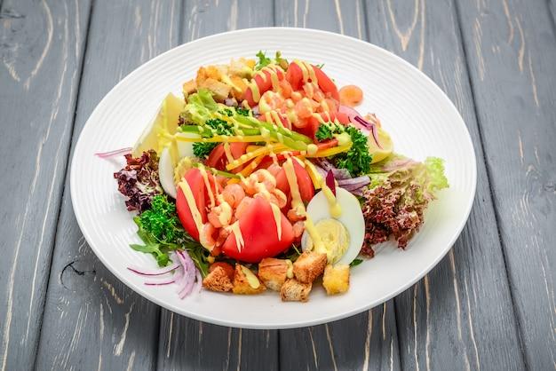 Caesar salad ai frutti di mare con gamberetti, foglia di insalata, crostini, formaggio ciliegia tomatond