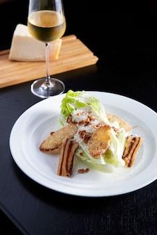 Caesar salad sul piatto bianco sulla tavola nera