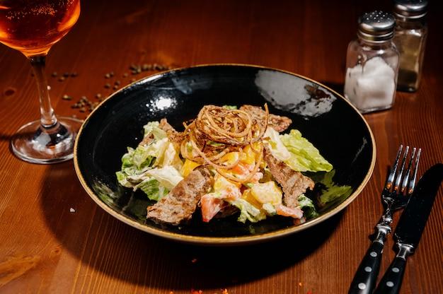 Caesar salad sulla banda nera sulla tavola di legno