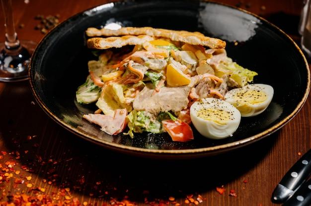 Caesar salad sulla banda nera sulla tavola di legno.