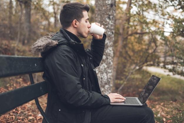 Caffè bevente del giovane con il computer portatile nel parco di autunno all'aperto. l'uomo con il computer portatile e il caffè in autunno parcheggiano sotto il fogliame di caduta.