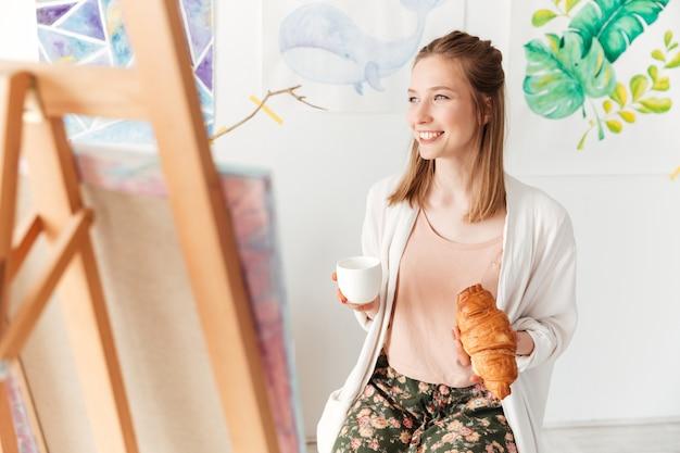 Caffè bevente del pittore felice di signora che mangia croissant