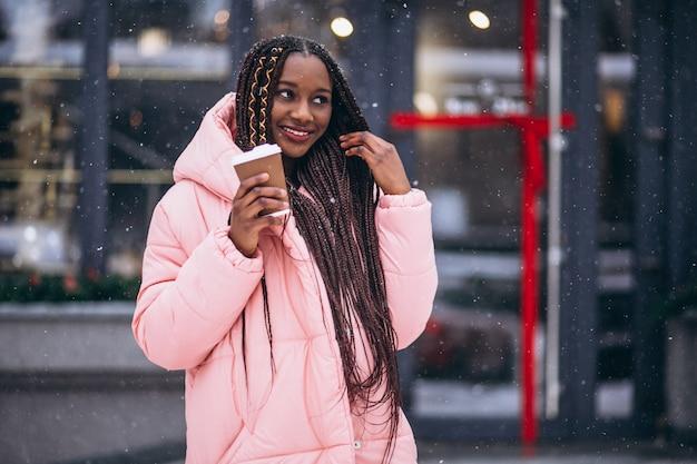Caffè bevente dell'afroamericano un giorno di inverno