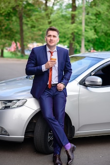 Caffè bevente dell'uomo d'affari nell'automobile.