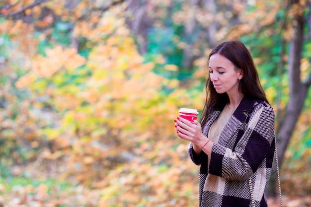 Caffè bevente della bella donna nel parco di autunno sotto il fogliame di caduta.