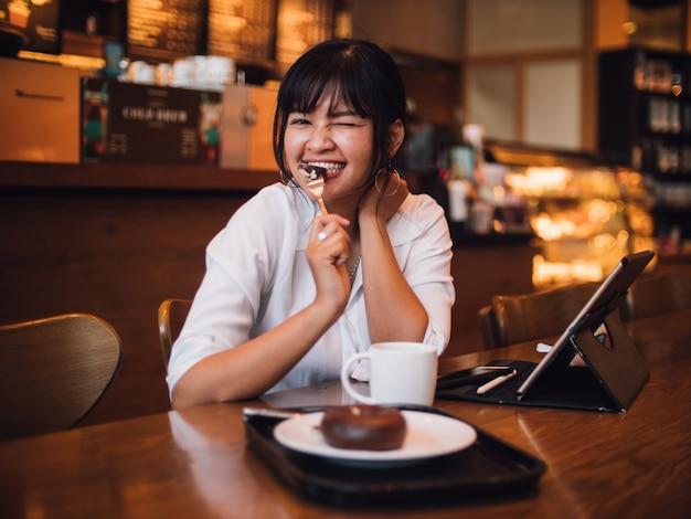 Caffè bevente della donna asiatica in caffè e computer portatile usando per l'affare lavorante