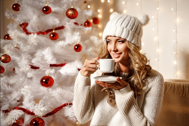 Caffè bevente della donna bionda felice, stanza interna con la decorazione di natale
