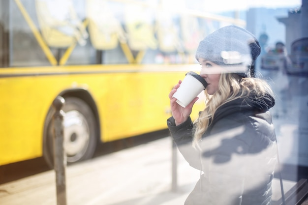 Caffè bevente della donna bionda in una fermata dell'autobus