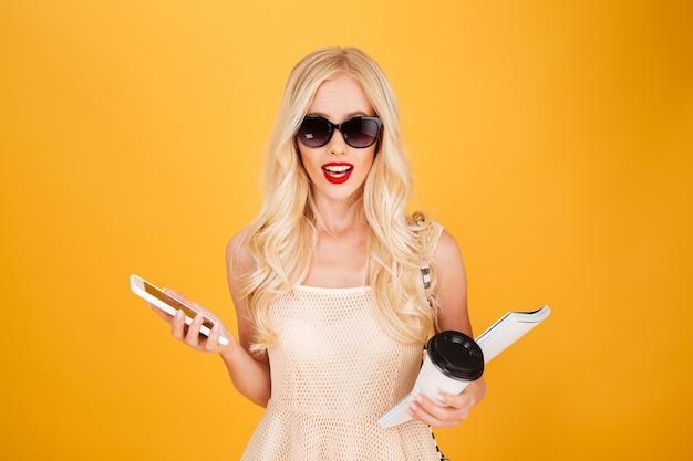 Caffè bevente della donna bionda stupefacente di giovane modo facendo uso del telefono.