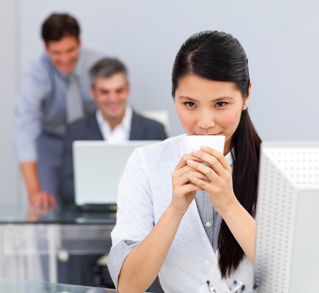 Caffè bevente della donna castana nell'ufficio
