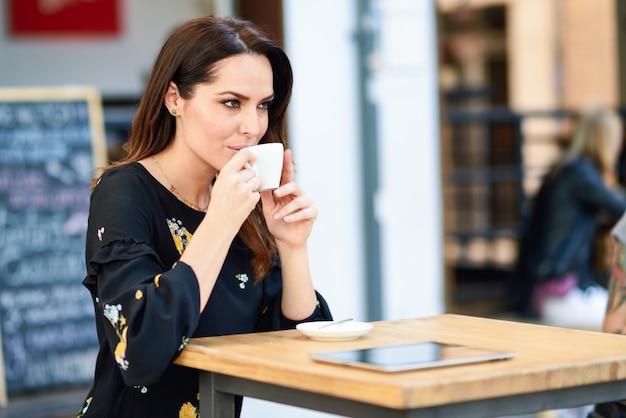 Caffè bevente della donna di mezza età in una barra di caffè urbana.