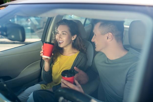 Caffè bevente della donna e del giovane in un'automobile