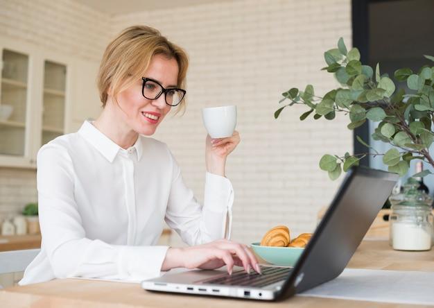 Caffè bevente della donna felice di affari mentre per mezzo del computer portatile