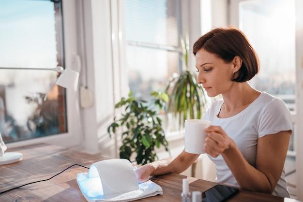 Caffè bevente della donna mentre asciugando le unghie