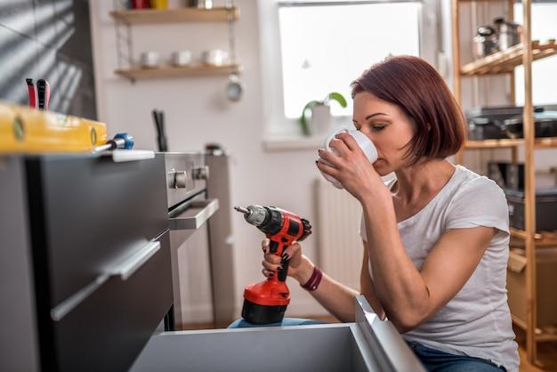 Caffè bevente della donna mentre costruendo un armadio da cucina