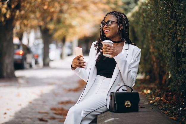 Caffè bevente della giovane donna africana e telefono usando