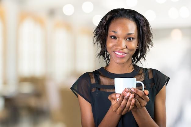Caffè bevente della giovane donna di affari africana mentre lavorando all'ufficio