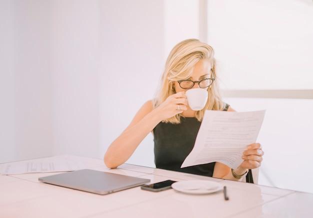 Caffè bevente della giovane donna di affari mentre leggendo il documento nell'ufficio