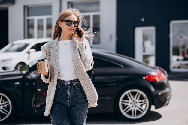 Caffè bevente della giovane donna felice in macchina
