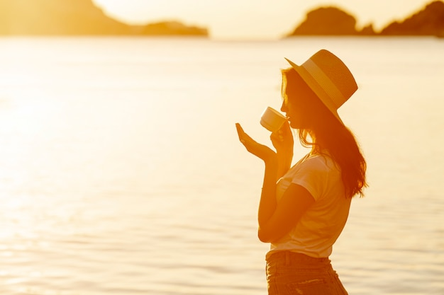 Caffè bevente della giovane donna sul tramonto